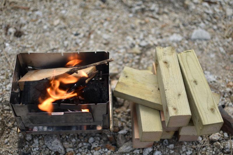 焚き火の近くに薪を置く